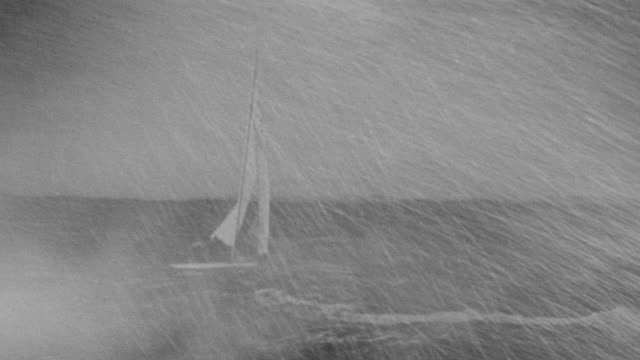 vidéos et rushes de ws shot of two people on sailboat at sea during heavy storm - navigation à voile