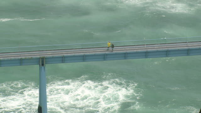 vidéos et rushes de ws aerial zo shot of two person talking with each other on bridge over sea / aquitaine, france - aquitaine