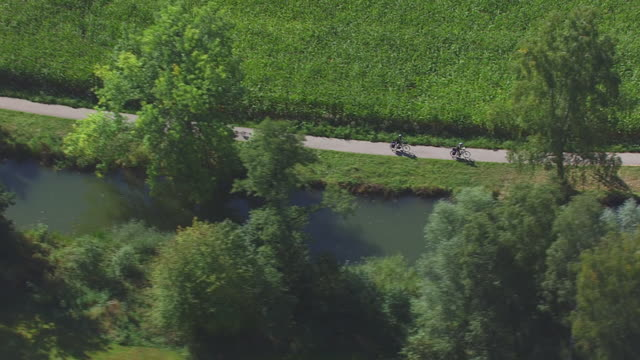 ws aerial ts shot of two rider riding bicycle on road / ellwangen, baden wurttemberg - baden wurttemberg stock videos and b-roll footage