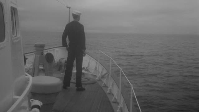 ms shot of two seaman enter and stand on the prow of the cutter and fishing boat approaches - marinaio video stock e b–roll