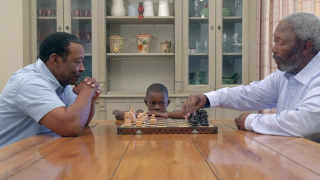 ms zi zo shot of two senior african men playing chess as grandchild watches / cape town, western cape, south africa - chess stock videos & royalty-free footage