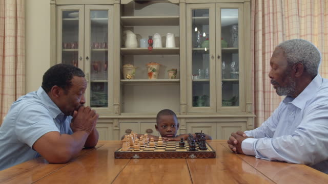 MS Shot of Two senior African men playing chess as grandchild watches / Cape Town, Western Cape, South Africa