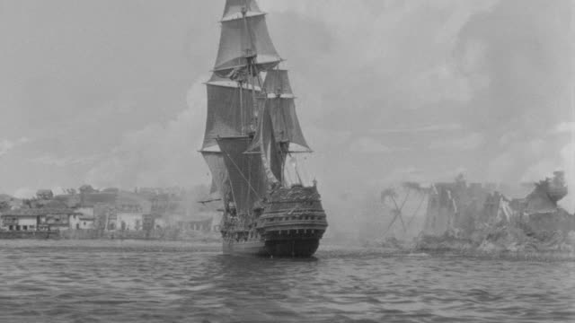 ms shot of two ships gun fighting at harbor - battle stock-videos und b-roll-filmmaterial