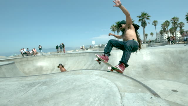 WS SLO MO Shot of two skateboarders doing front side air in skate park bowl and rail slide / Venice, California, United States