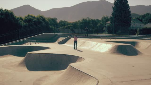 Shot of two skaters doing various tricks at the skatepark.