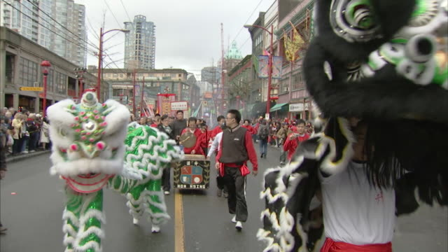 MS Shot of Two traditional lions dancing in parade AUDIO / Vancouver, British Columbia, Canada
