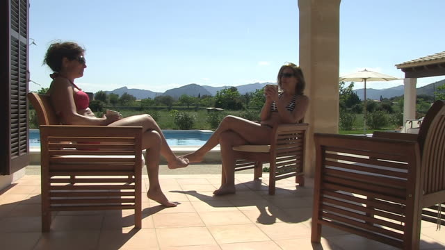 MS Shot of two woman drinking coffee at pool in holiday villa / Puerto Pollenca, Mallorca, Balearic Islands, Spain