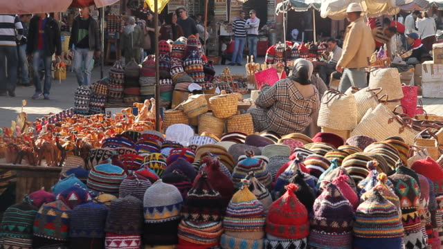 ms shot of two woman sitting at crafts tables with hand woven hats as people walking through area / marrakech, tensift, morocco  - korb stock-videos und b-roll-filmmaterial
