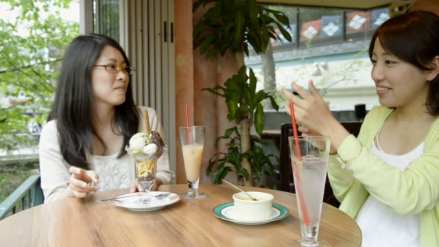 stockvideo's en b-roll-footage met ms shot of two women are taking pictures in cafã© with using smartphone / kyoto, japan - vredesteken handgebaar