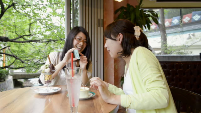 MS Shot of two women are taking pictures in café with using smartphone / Kyoto, Japan