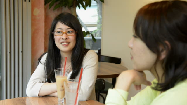 ms shot of two women are talking happily in cafã© / kyoto, japan - 歯を見せて笑う点の映像素材/bロール