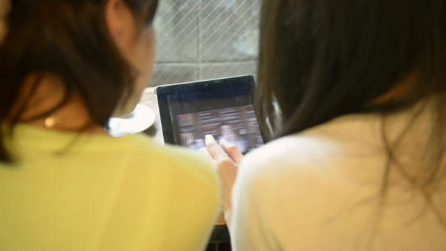 CU Shot of two women have seeing photos on digital tablet in café / Kyoto, Japan
