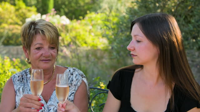CU Shot of two women having apero in beautiful garden / St. Remy de Provence, Provence, France