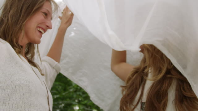 """""""ms la slo mo shot of two women laughing and playing under white sheet / berlin, germany"""" - 2k resolution stock videos and b-roll footage"""