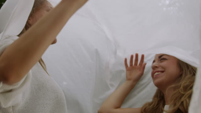 """""""ms slo mo shot of two women laughing and playing under white sheet / berlin, germany"""" - 2k resolution stock videos and b-roll footage"""
