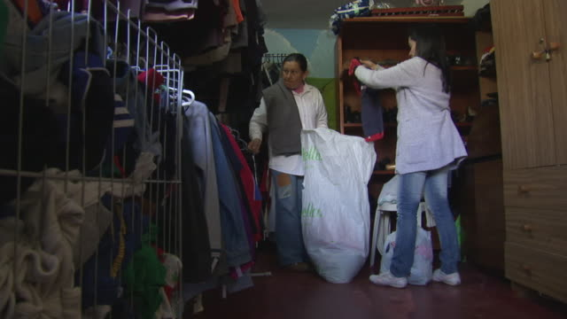 MS Shot of two women sort clothes into bags in a second hand store in the Ciudad Bolivar slum / Bogota, Colombia