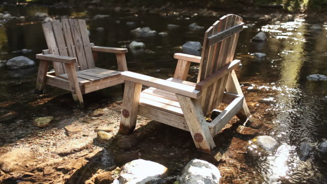 ms shot of two wooden adirondack chairs in flowing river / big sur, california, united states - アディロンダックチェア点の映像素材/bロール