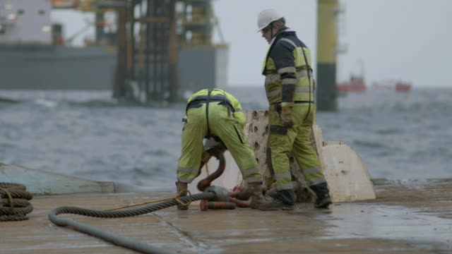WS PAN SLO MO Shot of two workers on deck of ship working with heavy wires Oil rig in / The North Sea
