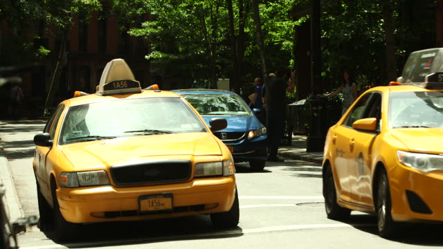 vídeos y material grabado en eventos de stock de shot of two yellow new york taxi cabs in greenwich village, ny - taxista