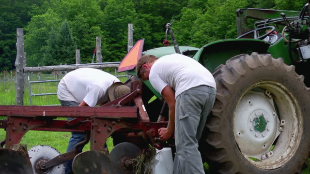 MS SLO MO TS Shot of Two young farmers hooking up farming equipment up to tractor / Chatham, Michigan, United States