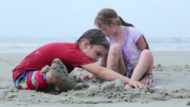 vidéos et rushes de ms tu shot of two young friends digging in sand at beach / st simon's island, georgia, united states - creuser