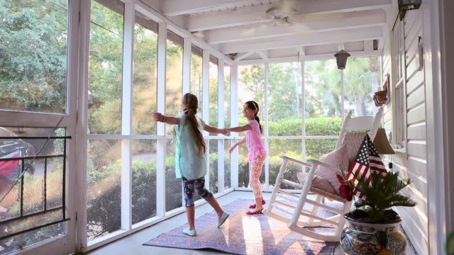 WS Shot of two young girls dancing together on screen porch / St Simon's Island, Georgia, United States