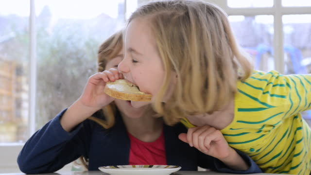 ms shot of two young girls having fun eating breakfast / london, greater london, united kingdom - prima colazione video stock e b–roll