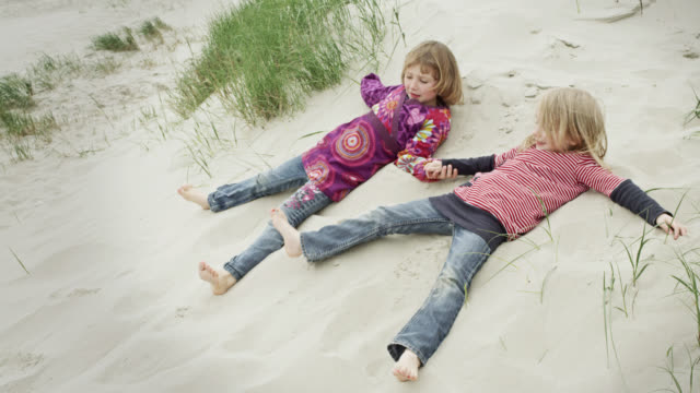 ms shot of two young girls lying in sand at beach, holding hands, then making sand angel / st. peter ording, schleswig holstein, germany  - reclining stock videos and b-roll footage