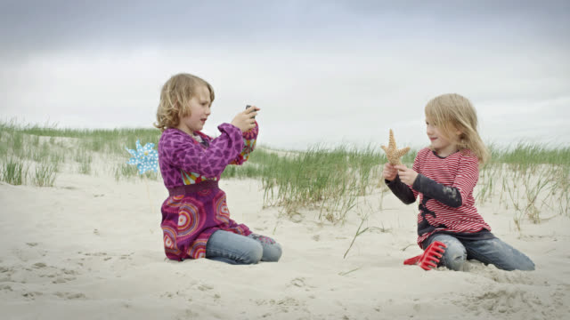 MS Shot of two young girls lying in sand at beach, one of them is holding starfish and other one is taking photo of her / St. Peter Ording, Schleswig Holstein, Germany