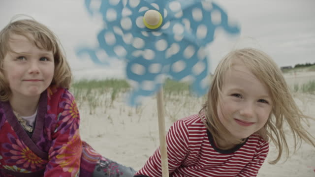 vídeos de stock e filmes b-roll de cu shot of two young girls lying in sand at beach smiling and holding small wind mill / st. peter ording, schleswig holstein, germany  - moinho de papel