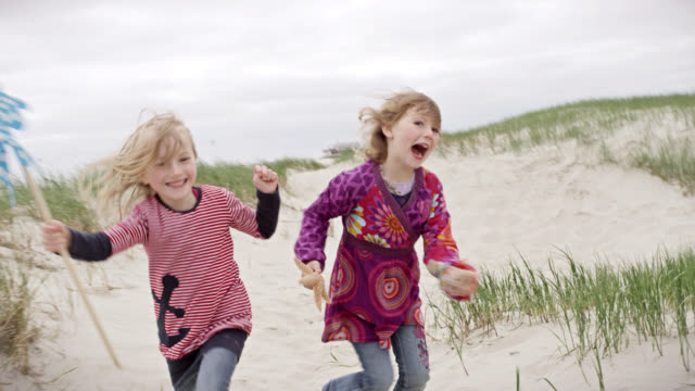 ms pov shot of two young girls running in sand at beach smiling, one of them is holding small wind mill and other one holding star fish / st. peter ording, schleswig holstein, germany  - children only stock videos & royalty-free footage
