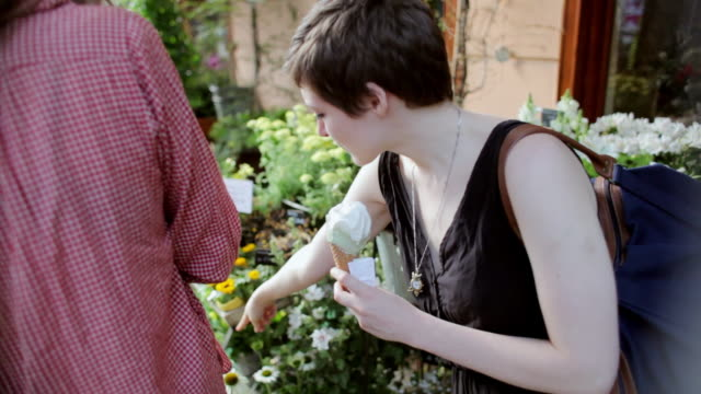 """""""MS Shot of Two young woman eating ice cream in front of flower shop / Berlin, Germany"""""""