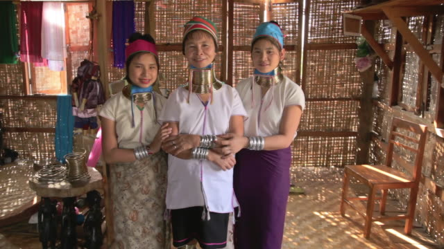ms shot of two young women and elderly woman wearing neck rings looking at camera smiling and standing side by side / inle lake, shan state, myanmar  - side by side stock videos & royalty-free footage
