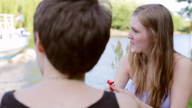"""cu shot of two young women sitting by spree river, picnicking and eating strawberries / berlin, germany"" - picnic stock videos & royalty-free footage"