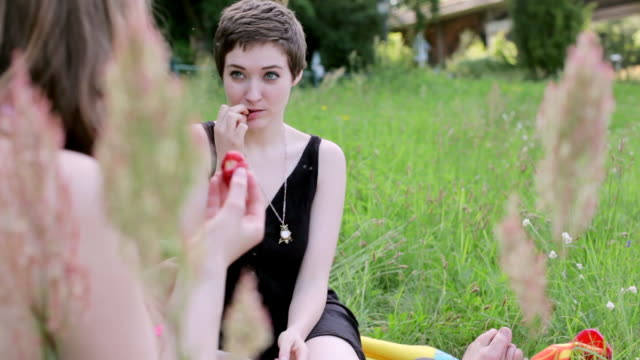 'MS Shot of Two young women sitting by Spree river, picnicking and eating strawberries / Berlin, Germany'