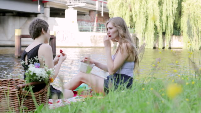 "vídeos de stock e filmes b-roll de ""ms shot of two young women sitting by spree river, picnicking and eating strawberries / berlin, germany"" - picnic"