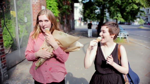 "vidéos et rushes de ""ms pov shot of two young women walking down street with flowers and ice cream / berlin, germany"" - tentation"