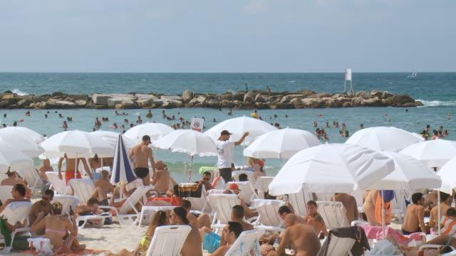 ws shot of typical crowded beach / tel aviv, dan metropolitan,gush dan, israel - テルアビブ点の映像素材/bロール