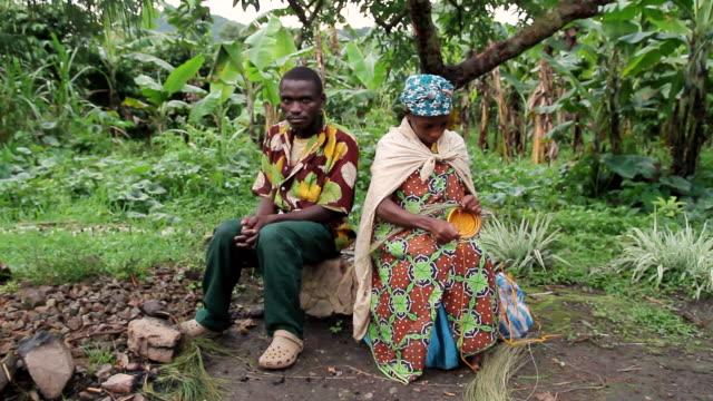 ms shot of ugandan man and woman sitting on log, man looking towards and woman  weaving  basket / kigez, kabale, uganda - wiese stock videos & royalty-free footage