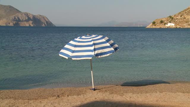 ms shot of umbrella at nimborios bay  / symi, dodecanese islands, greece - beach umbrella stock videos and b-roll footage