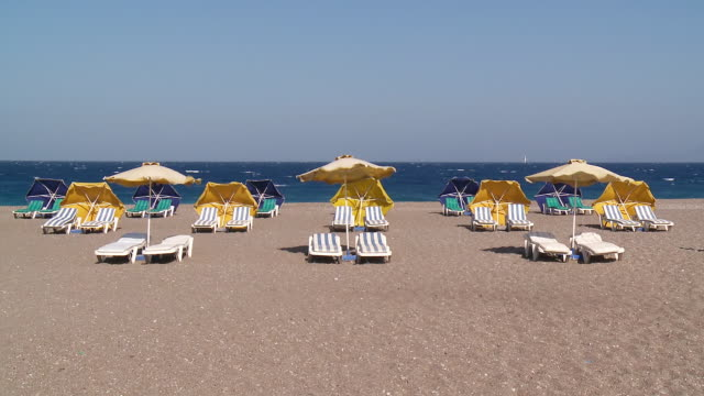 MS Shot of Umbrellas and Deckchairs in Wind  Beach of west side Town / Rhodes, Dodecanese islands, Greece