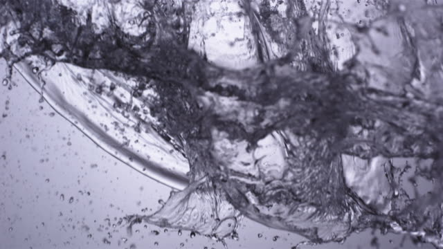 CU SLO MO Shot of uncontrolled wave of water falling through frame against grey blue back drop / United Kingdom