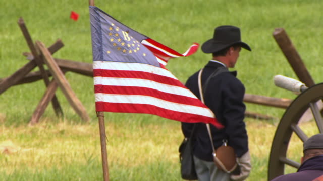 CU Shot of Union Round Pattern flag in foreground with soldiers preparing to fire canon shot during Battle of Gettysburg / Gettysburg, Virginia, United States