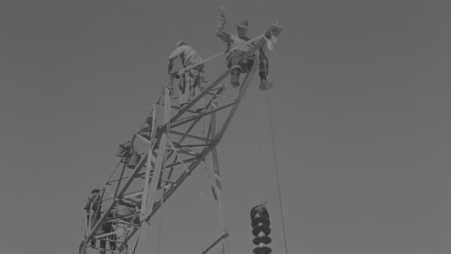 ms shot of up angle to crew of men working on eclectic tower and power lines. - electricity stock videos & royalty-free footage