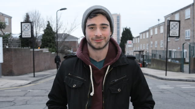 vidéos et rushes de ms shot of urban man smiling on street / london, greater london, united kingdom - regardant l'objectif