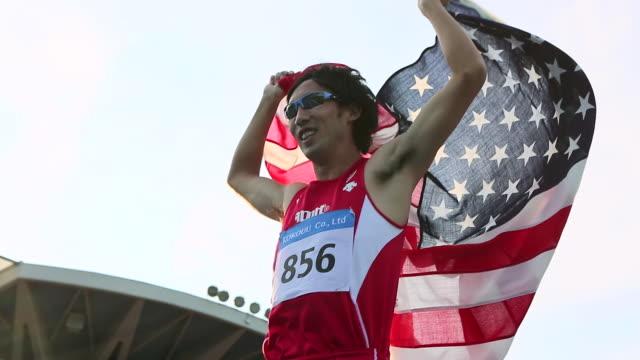 cu la ts shot of us athlete with national flag / tokyo, japan - sunglasses点の映像素材/bロール