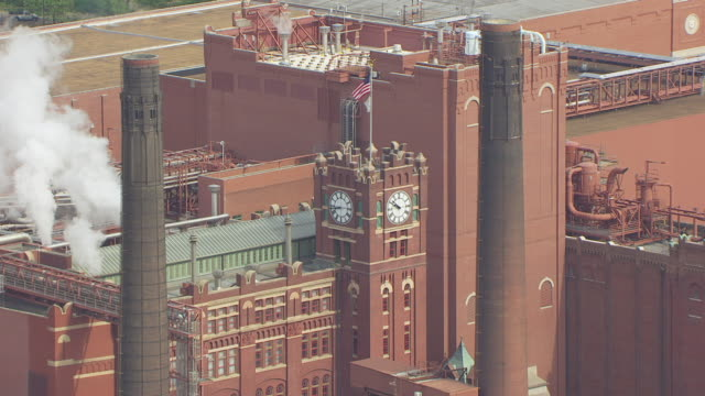 MS AERIAL TS ZO TD Shot of US flags on clocktower then reveal buildings at Anheuser Busch brewery / St Louis, Missouri, United States