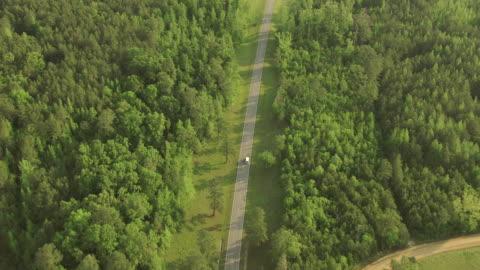 vídeos y material grabado en eventos de stock de ws aerial zi ts shot of van on road through countryside with trees in choctaw county / mississippi, united states - vehículo terrestre