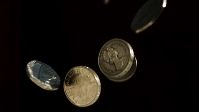 CU SLO MO Shot of various British sterling coins falling and bouncing
