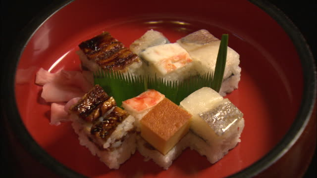 shot of various types of hakozushi (box sushi) on a wooden plate in osaka, japan - rectangle stock videos & royalty-free footage